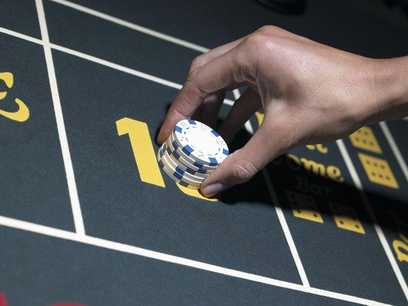 Hand placing gamingchips on a craps table.
