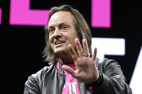 John Legere holding his hand out while speaking on stage