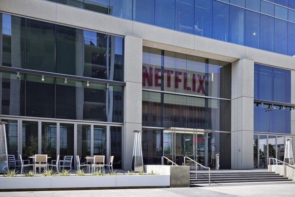 The glass front face of a building with the Netflix logo above the door.
