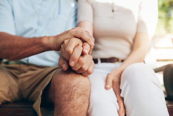 Loving couple sitting together and holding hands
