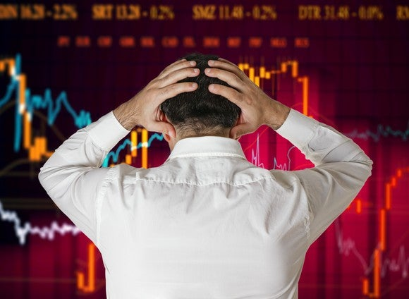 A man puts his hands  on his head while staring at volatile stock charts