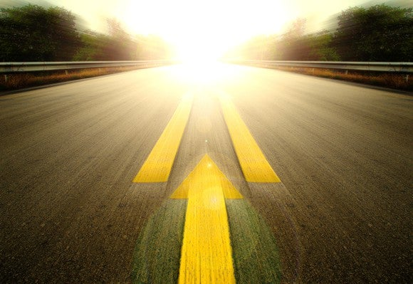 An arrow pointing forward on a road that's leading towards a bright light