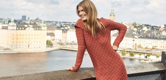 A woman in a long sweater poses by the water.