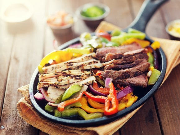 Beef and chicken fajitas, served on a skillet