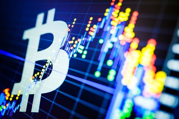 Bitcoin symbol in front of a candlestick price chart.