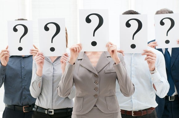 Five people holding sheets with question marks in front of their faces