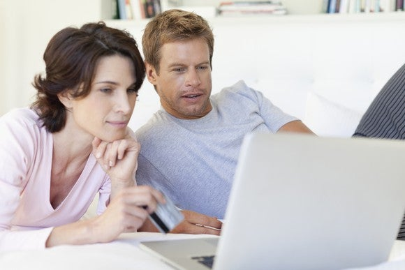 40-something couple lounging side by side while browsing on a laptop