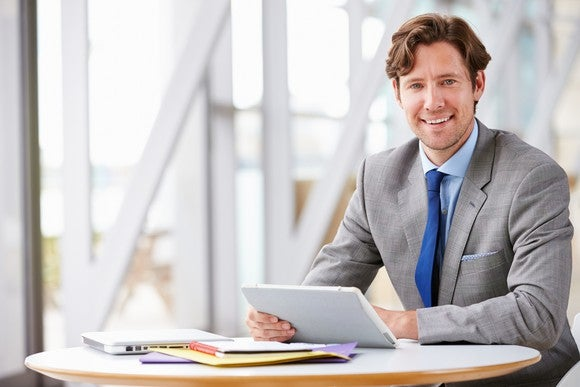 Smiling man in business suit sits at a small round table, holding a tablet, with a laptop and papers spread out in front of him.