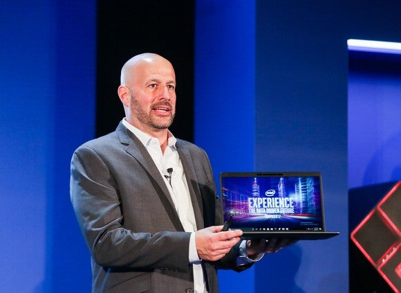 Intel executive Gregory Bryant holding a laptop.