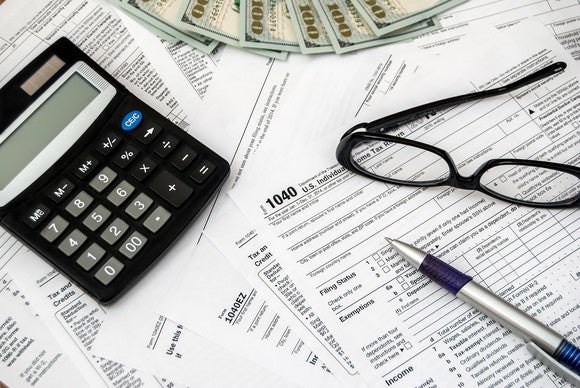 Tax forms, cash, a calculator, glasses, and a pen spread out on a surface.