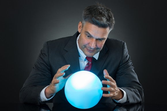 Man in a suit looks into a bright blue crystal ball.