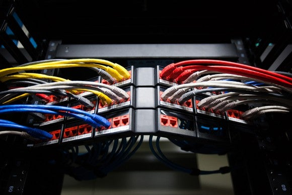 Many brightly colored networking cables, plugged into several switches shown at an angle.