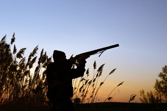 Hunter shooting at prey in field.