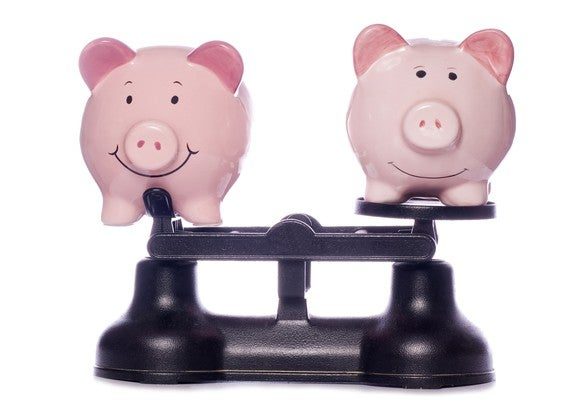 Two piggy banks on scales