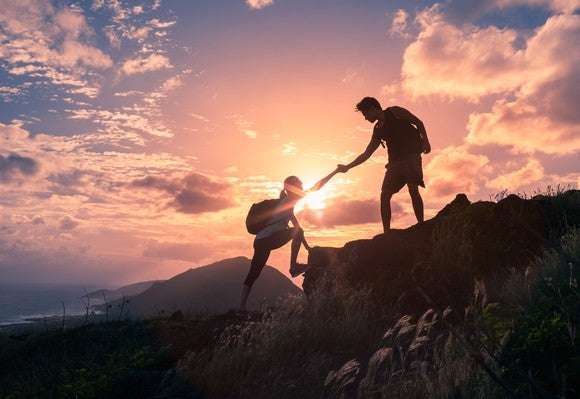 Male and female hikers climbing up a mountain cliff and one of them giving a helping hand