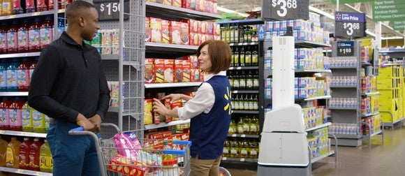 A Wal-Mart employee talks with a customer with a Bossa Nova robot scanning the next aisle.