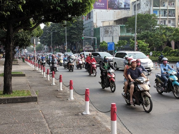 A street in Vietnam crowded with motorbikes and a couple of cars. Some bikes have two or more riders each.