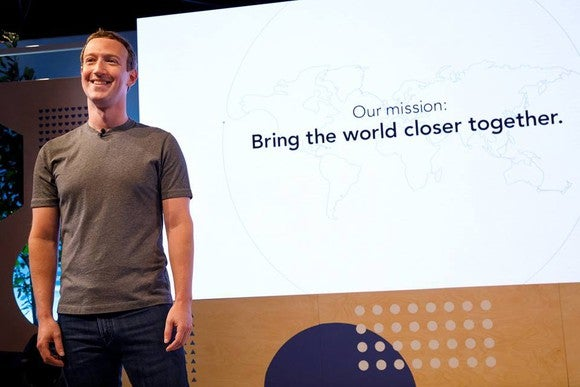 Zuckerberg standing on stage with company's mission displayed behind him