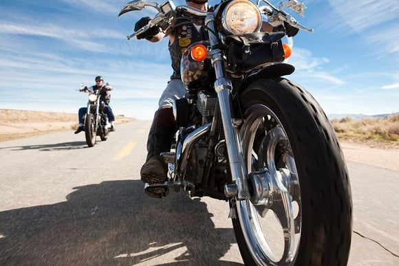 Two people riding motorcycles on highway.