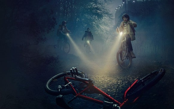 Three of the main characters from Stranger Things, shining their flashlights over a red bicycle on a misty night.