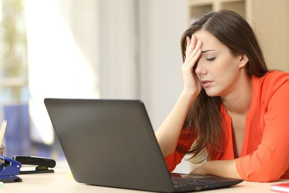 A woman puts her hand on her head in front of a laptop.