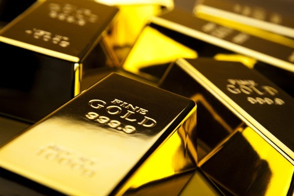 Several glittering gold bars lie next to each other.