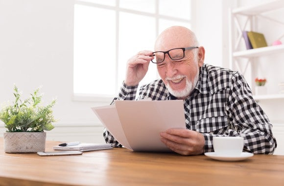 Senior man holding papers and lifting up glasses on his face