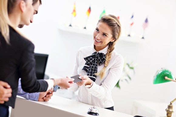 A woman behind a counter handing a cardkey to another woman.