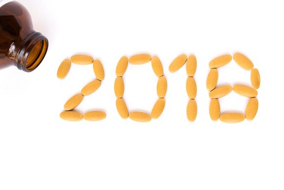 The number 2018 formed with pills, with a brown pill bottle in the corner.