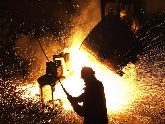 A steel worker operating equipment in a foundry.