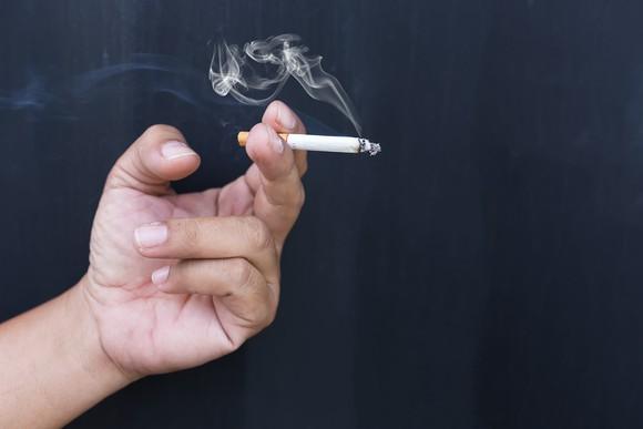 Hand holding a lit cigarette.