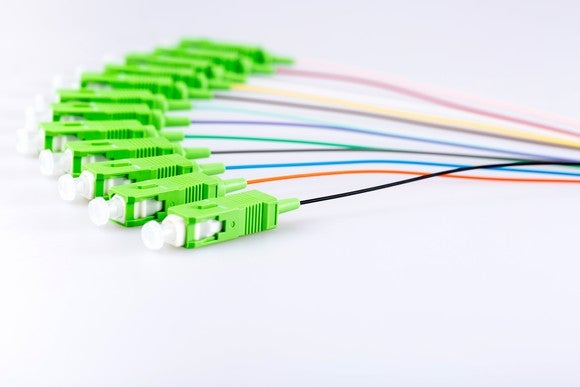 A bundle of fiber-optic network cables fanned out on a white table.
