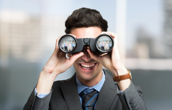 Businessman looking into binoculars.