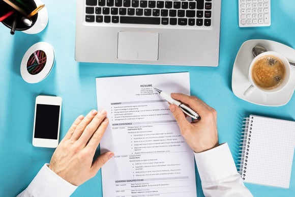A resume is shown on a crowded desk.