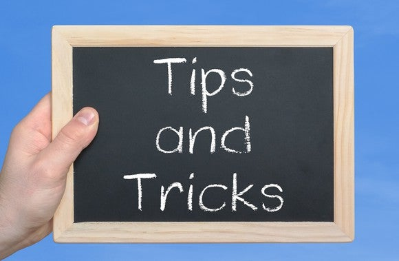 hand holding small blackboard on which is written tips and tricks