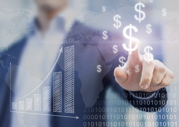 A businessman points at dollar signs floating in front of him on a monitor.