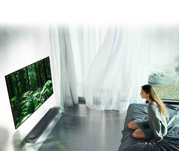"A woman sitting on a bed watching a 77"" OLED TV from LG."
