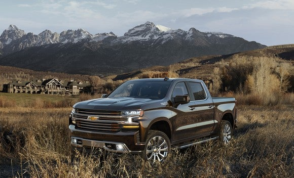 A 2019 Chevrolet Silverado High Country pickup truck in a field, with mountains and a building in the background.