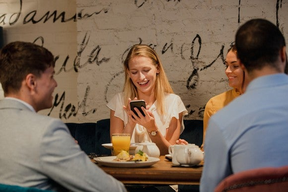Friends dining in restaurant, woman holding mobile phone and smiling
