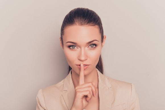 A businesswoman holding her finger to her lips.