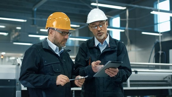 Men in hard hats looking at a tablet.