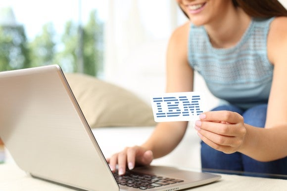 A young woman using her laptop with one hand, holding a card with the iconic IBM logo in the other.