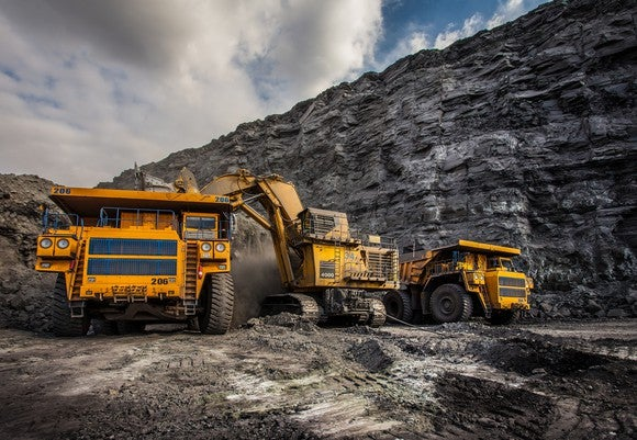 Several mining trucks operating at a site.