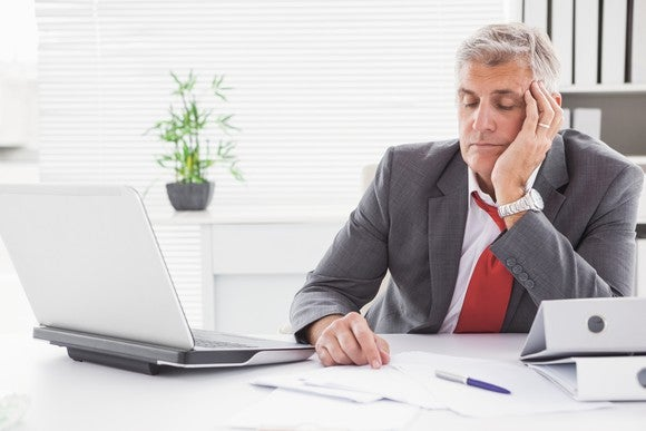 Man in business suit falling asleep at his desk