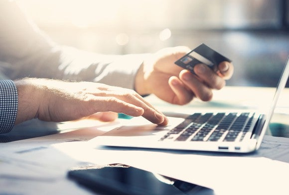 Person holding a credit card at a laptop