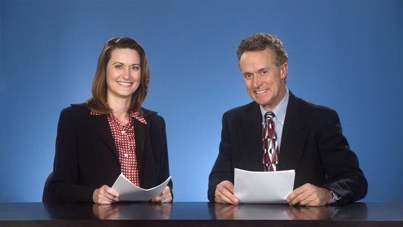A woman and man, both smiling and dressed in suits, sit behind a desk with papers in hand looking at the camera.