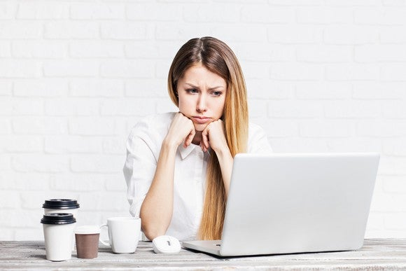 Woman at a laptop, looking sad