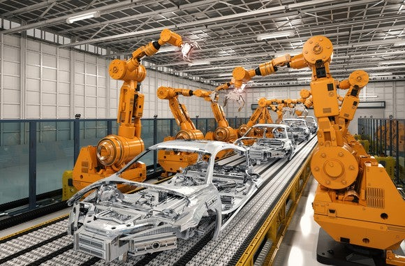 Robotic arms working along both sides of an auto assembly line, with several car frames on it.
