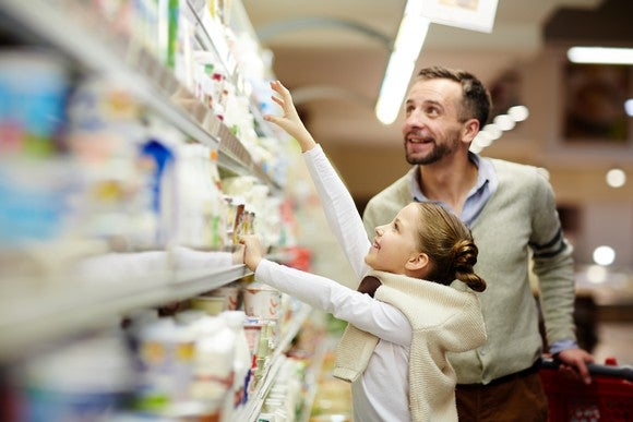 A man and a young girl picking up items from a store shelf.