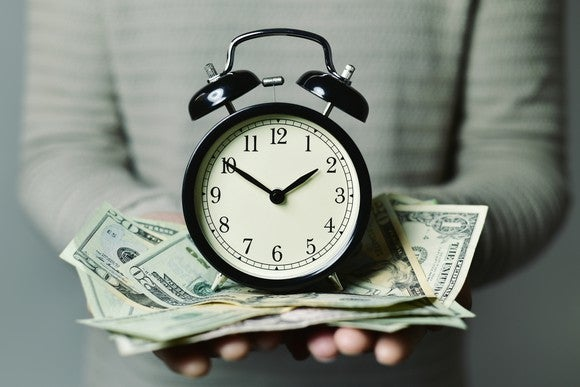 A person holding a clock on top of a pile of money.